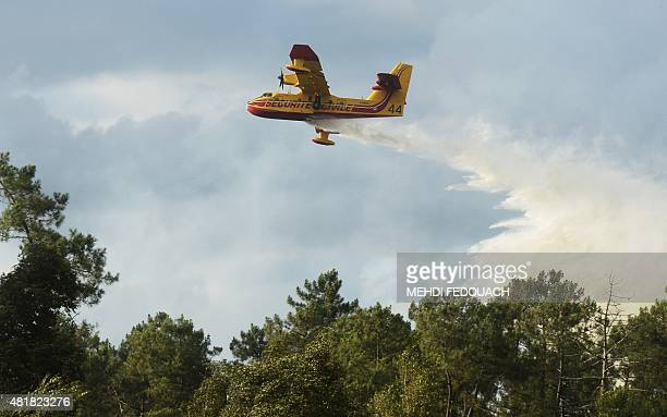 A Canadair water bomber aircraft drops water as firefighters try to extinguish a forest fire that broke out near SaintJean d'Illac some 20km of...