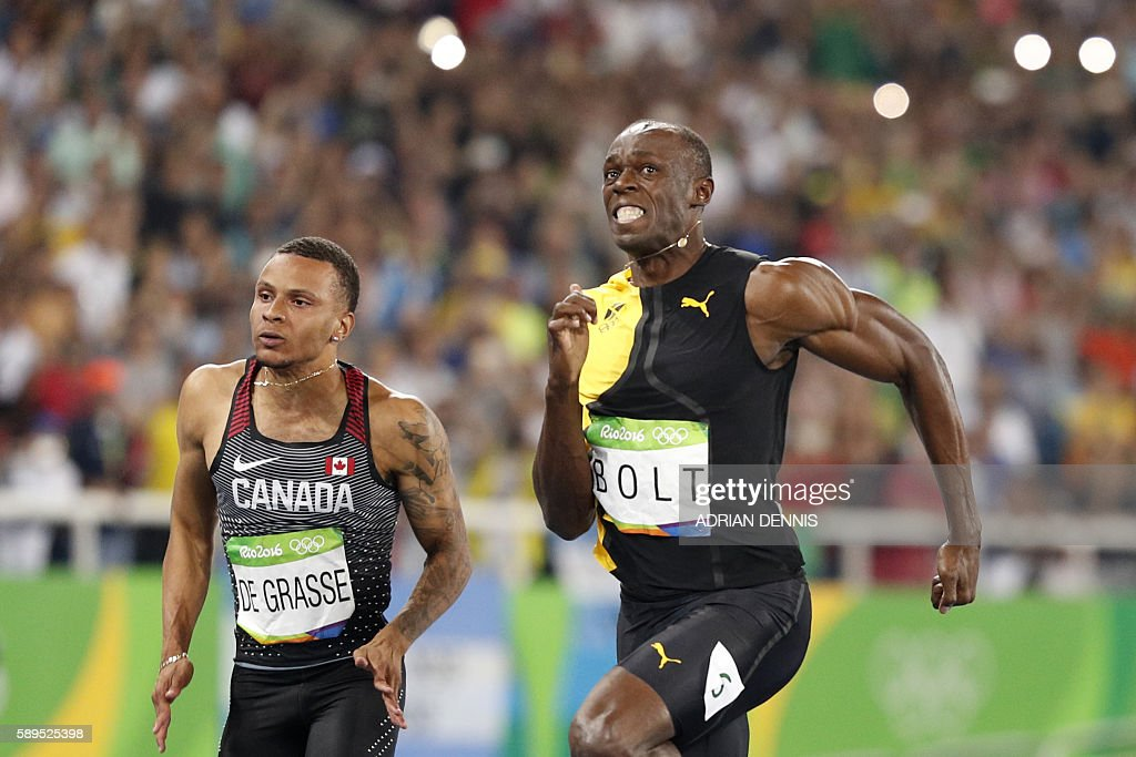 TOPSHOT - Canada's Andre De Grasse (L) and Jamaica's Usain Bolt compete in the Men's 100m Final during the athletics event at the Rio 2016 Olympic Games at the Olympic Stadium in Rio de Janeiro on August 14, 2016. / AFP / Adrian DENNIS