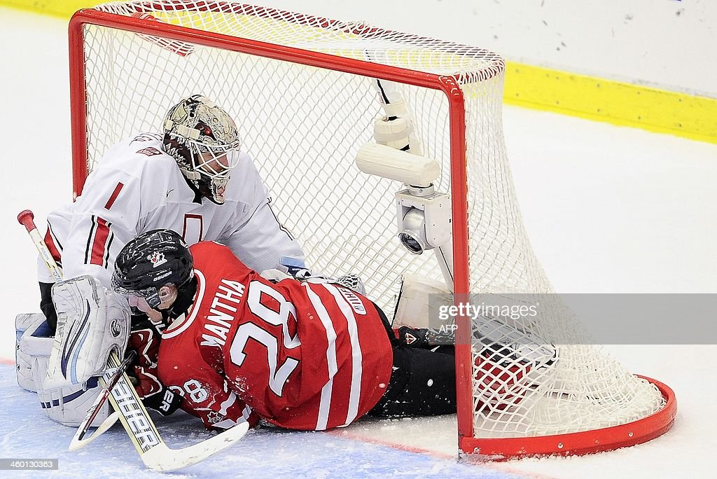 Canada's Anthony Mantha falls into the goalmouth of Switzerland's goalie Melvin Nyffeler after Mantha scored a penalty 2-0 during the World Junior Hockey Championships quarter final between Canada and Switzerland at the Malmo Stadium in Malmo, Sweden, on January 2, 2014.