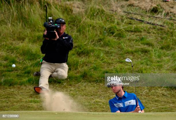 Canada's Austin Connelly chips from a greenside bunker to the 7th green during his final round on day four of the 2017 Open Golf Championship at...