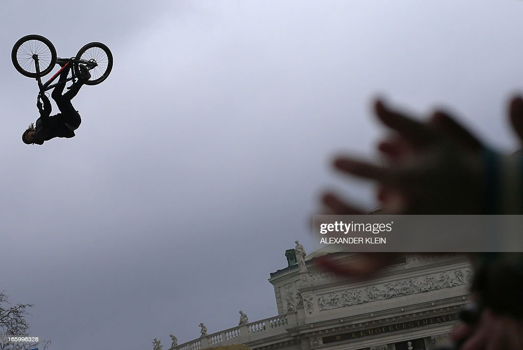 Canada's Brett Rheeder is silhoueted as he jumps in the air with his bike as children clap in their hands to cheer, as he competes during the Red Bull Vienna Air King dirt jumping competition held in front of the Rathaus (townhall) and the Burgtheater in Vienna on April 7, 2013. Canada's Brett Rheeder won the 2013 edition which is held every spring in the Austrian capital, and marks the season opening of the Freeride Mountain Bike (FMB) World Tour. AFP PHOTO / ALEXANDER KLEIN