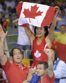 Canada's Carol Huynh celebrates with team officials after defeating Japan's Chiharu Icho during their women's 48kg gold medal match at the 2008...