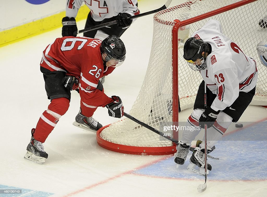 Canada's Curtis Lazar (L) manages to get the puck into the net behind Switzerland's Kevin Fiala during the World Junior Hockey Championships quarter final between Canada and Switzerland at the Malmo Stadium in Malmo, Sweden on January 2, 2014. Canada won the match 4-1 and is ready for the semifinal Saturday.