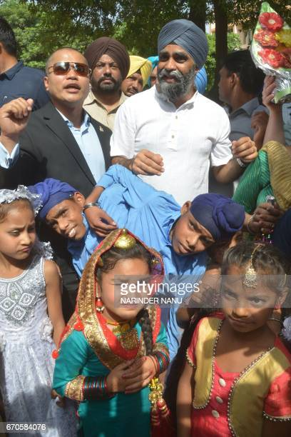 Canada's Defence Minister Harjit Singh Sajjan poses conjoined twins Sona and Mona adopted by the All India Pingalwara Charitable Society at Manawala...