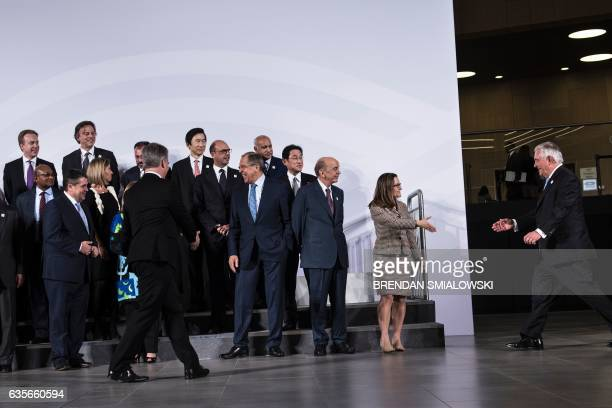 Canada's Foreign Minister Chrystia Freeland reaches to shake US Secretary of State Rex Tillerson's hand as he arrives last for a group photo of G20...