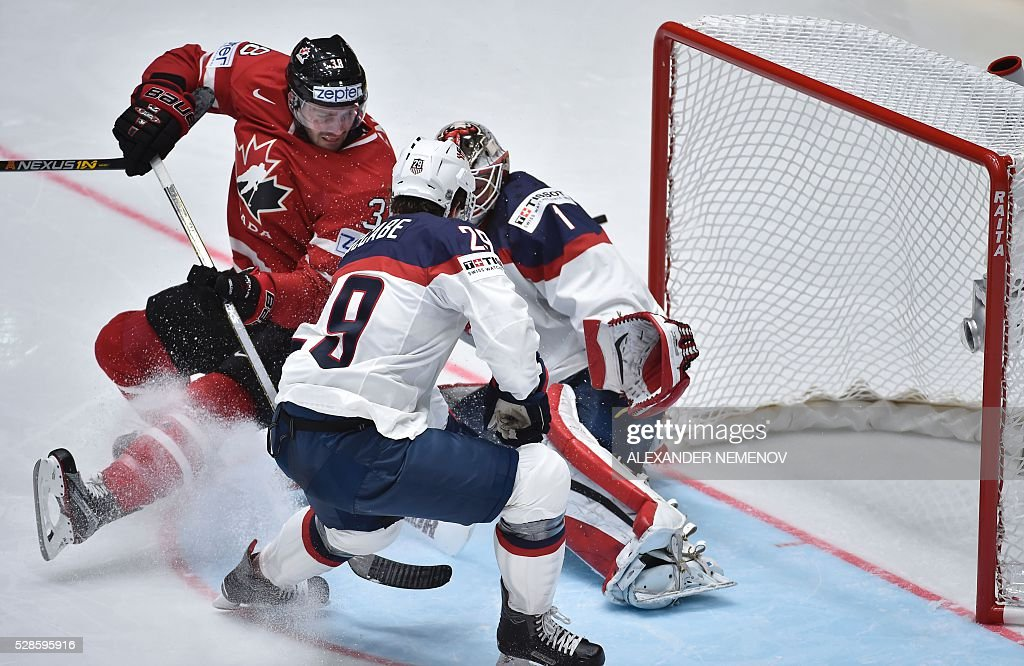 Canada's forward Boone Jenner (L) attacks the net of US goalie Keith Kinkaid during the group B preliminary round game USA vs Canada at the 2016 IIHF Ice Hockey World Championship in St. Petersburg on May 6, 2016. / AFP / ALEXANDER