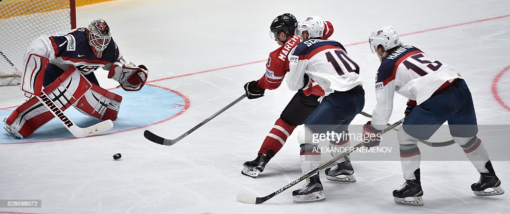 Canada's forward Brad Marchand (C) scores past US goalie Keith Kinkaid during the group B preliminary round game USA vs Canada at the 2016 IIHF Ice Hockey World Championship in St. Petersburg on May 6, 2016. / AFP / ALEXANDER