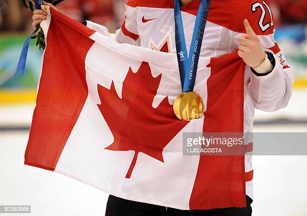 Canada's forward Haley Irwin celebrates wearing her gold medal and holding the national flag during the medals ceremony following their win over the...