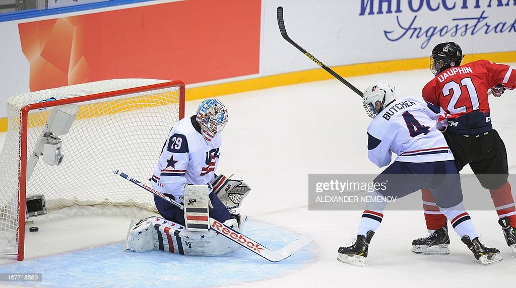 Canada's forward Laurent Dauphin (R) scores past US goalkeeper Thatcher Demko (L) and US defenser Will Butcher (C) during the IIHF U18 International Ice Hockey World Championships final game in Sochi on April 28, 2013.
