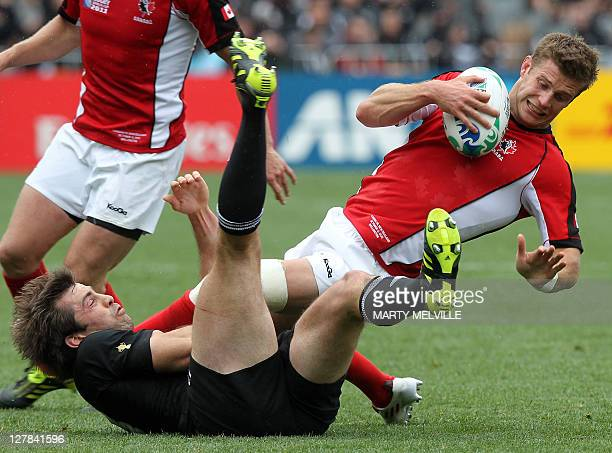 Canada's full back Matt Evans is tackled by New Zealand All Black center Conrad Smith as Canada's flyhalf Ander Monro looks on during the 2011 Rugby...