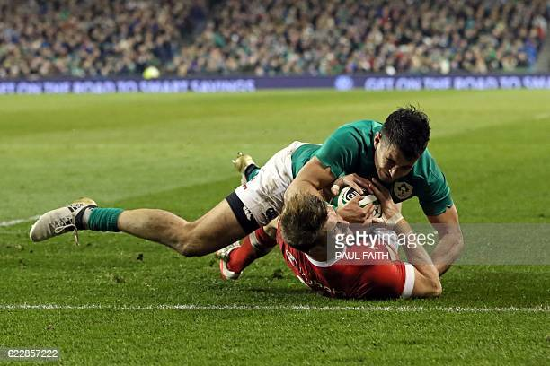 TOPSHOT Canada's fullback Matt Evans manages to beat Ireland's fullback Tiernan O'Halloran to score a try during the rugby union test match between...