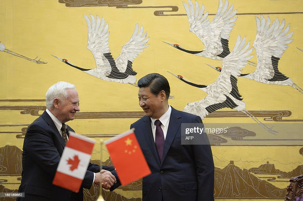 Canada's Governor General David Johnston (L) shakes hands with Chinese President Xi Jinping (R) after a signing ceremony at the Great Hall of the People in Beijing on October 18, 2013. Johnston's visit is aimed at boosting relations between Canada and China.