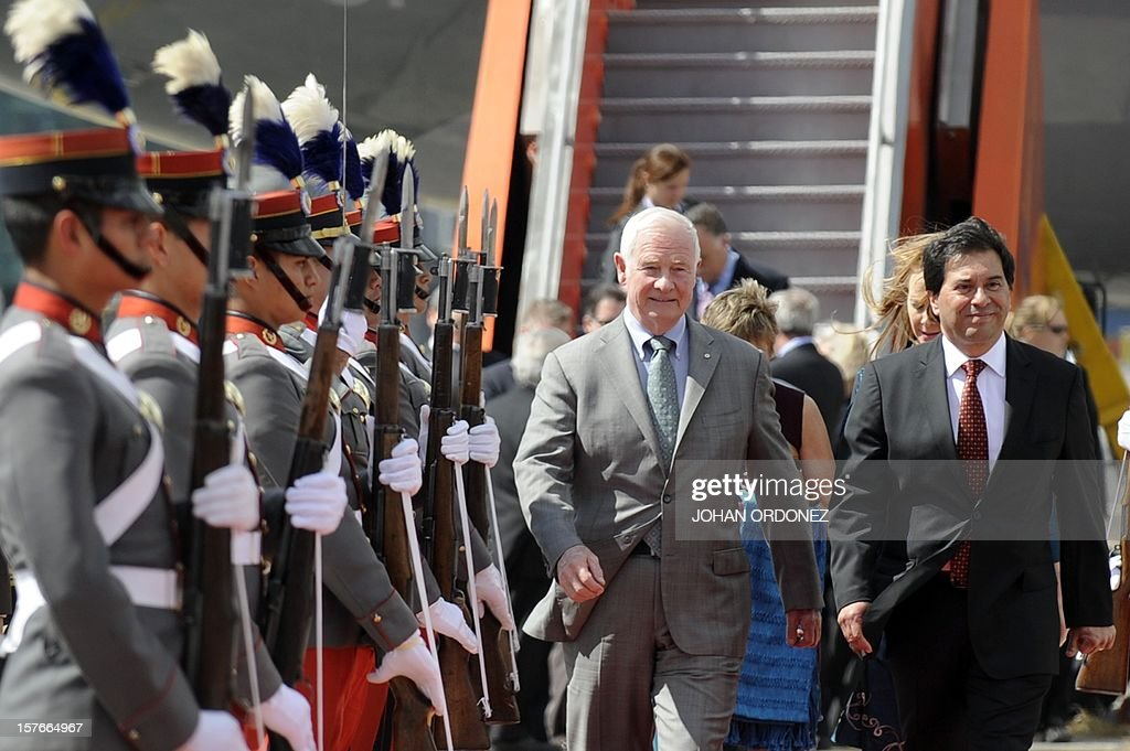 Canada's Governor General David Lloyd Johnston (L) and Guatemalan Foreign Minister Harold Caballeros receive military honors upon the former's arrival at the air force base in Guatemala City on December 5, 2012. AFP PHOTO / Johan ORDONEZ