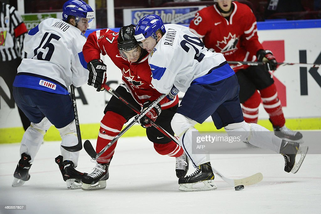 Canada's Jonathan Drouin (2nd L) vies with Finland's Juuso Vainio (L) and Otto Rauhala (R) during the World Junior Hockey Championships semifinal between Canada and Finland at Malmo Arena in Malmo, Sweden on January 4, 2014.