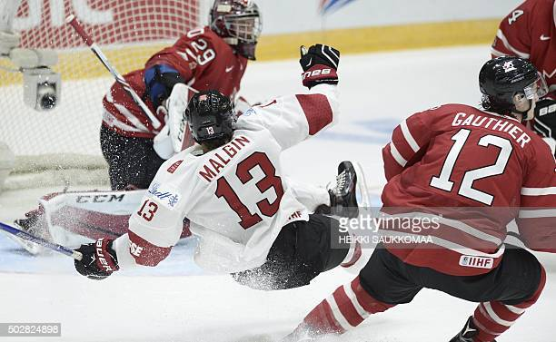 Canada's Julien Gauthier tackles Switzerland's Denis Malgin at the goal of Canada's goalie Mackenzie Blackwood during the 2016 IIHF World Junior U20...