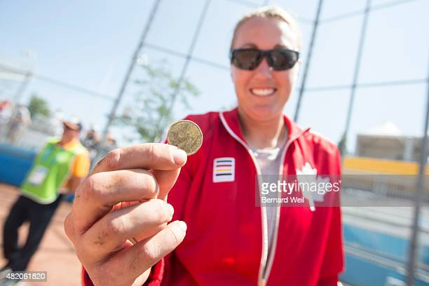 AJAX ON JULY 26 Canada's Kaleigh Rafter holds a loonie that was buried at home plate Canada played the USA for gold medal in softball Canada won 42...
