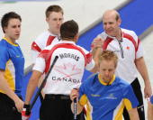 Canada's Kevin Martin celebrates his team's victory with John Morris and Marc Kennedy while Sweden's Fredrik Lindberg and Niklas Edin look on after...