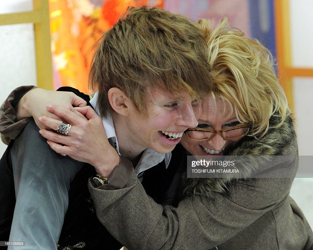 Canada's Kevin Reynolds (L) celebrates his score with his coach after his free skating performance in the men's event during the Four Continents figure skating championships in Osaka on February 9, 2013. AFP PHOTO / TOSHIFUMI KITAMURA
