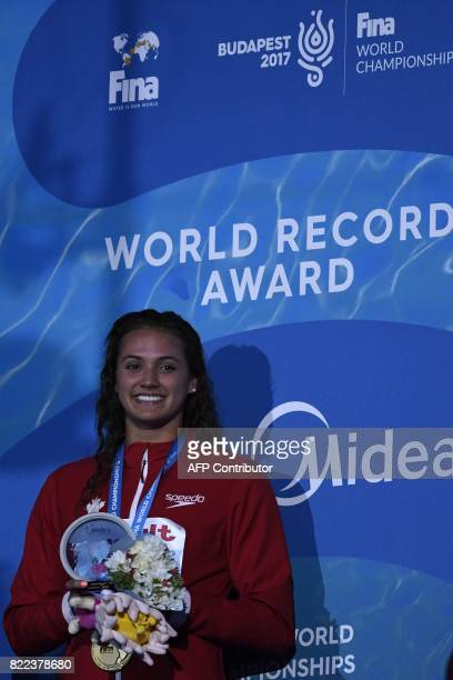 Canada's Kylie Jacqueline Masse celebrates her new world record on the podium after the women's 100m backstroke final during the swimming competition...
