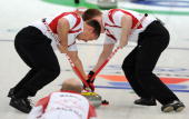 Canada's Marc Kennedy and Ben Hebert sweep for the throw by skip Kevin Martin during the Canada vs Sweden men's curling semifinal match at the...