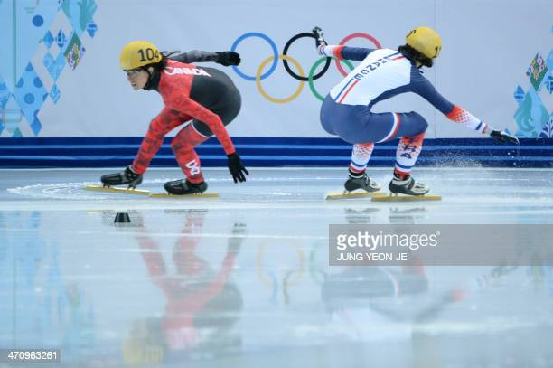 Canada's MarieEve Drolet compets as France's Veronique Pierron falls in the Women's Short Track 1000 m Quarterfinals at the Iceberg Skating Palace...