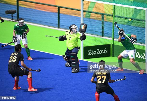 TOPSHOT Canada's Matthew Guest and Canada's Sukhi Panesar look on a a goal is scored during the men's field hockey Ireland vs Canada match of the Rio...