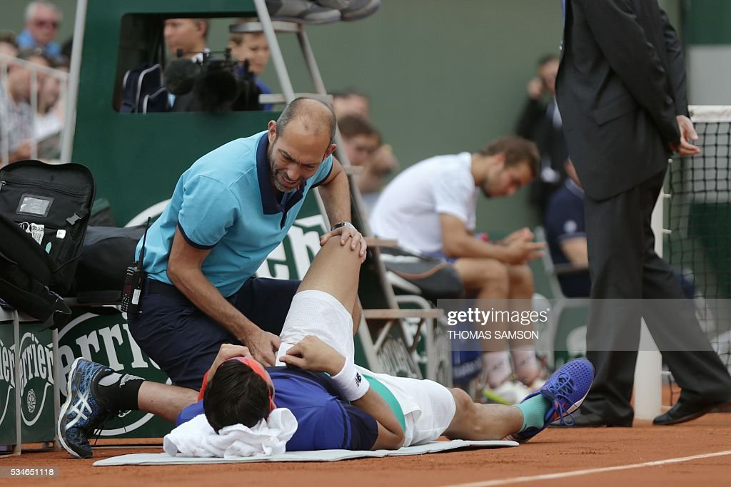 Canada's Milos Raonic receives treatment during his men's third round match against Slovakia's Andrej Martin at the Roland Garros 2016 French Tennis Open in Paris on May 27, 2016. / AFP / Thomas SAMSON