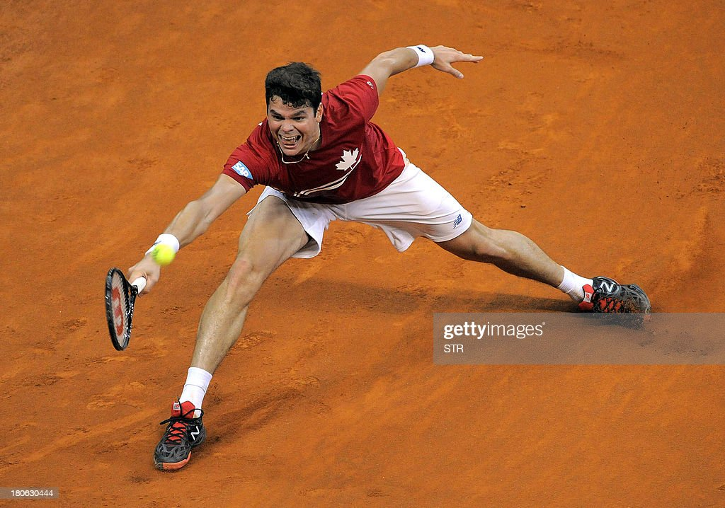 Canada's Milos Raonic returns the ball to Serbia's Novak Djokovic during their Davis Cup semi-final match at Belgrade Arena on September 15, 2013. Djokovic kept Serbia alive in the Davis Cup semi-final match against Canada by defeating Raonic 7-6 (7/1), 6-2, 6-2.