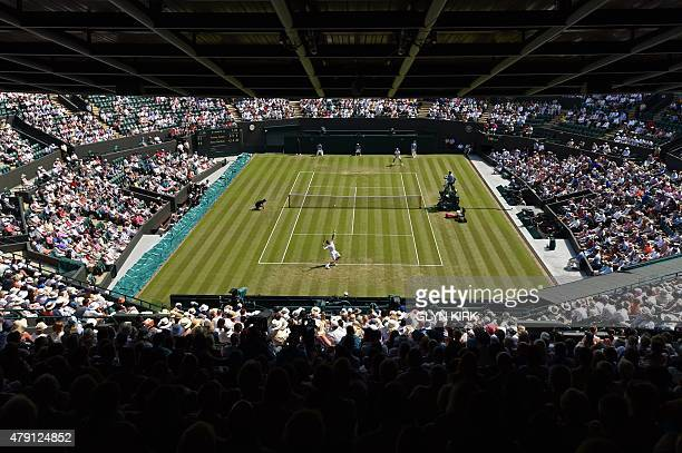 Canada's Milos Raonic serves to Germany's Tommy Haas during their men's singles second round match on day three of the 2015 Wimbledon Championships...