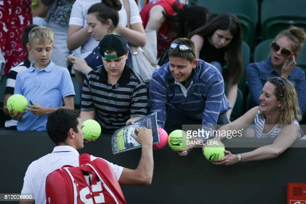 Canada's Milos Raonic signs autographs after beat Germany's Alexander Zverev during their men's singles fourth round match on the seventh day of the...