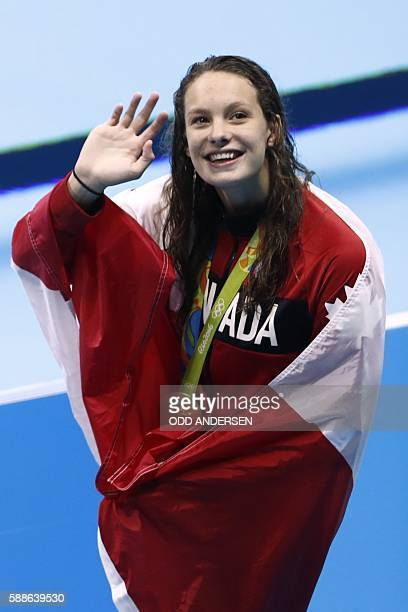 Canada's Penny Oleksiak waves while wrapped in her national flag during the medal ceremony of the Women's 100m Freestyle Final during the swimming...