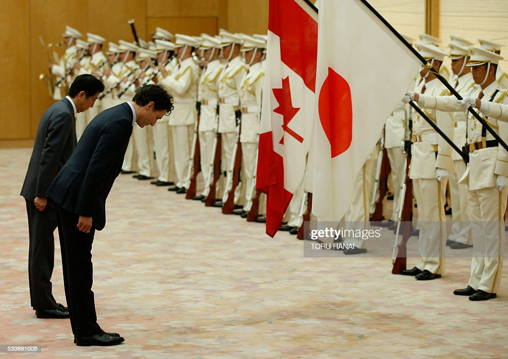 Canada's Prime Minister Justin Trudeau (2nd L) bows with Japan's Prime Minister Shinzo Abe (L) as they review a guard of honour before their meeting at Abe's official residence in Tokyo on May 24, 2016. Trudeau stopped in Tokyo before attending the Ise-Shima G7 Summit on May 26-27. / AFP / POOL / TORU