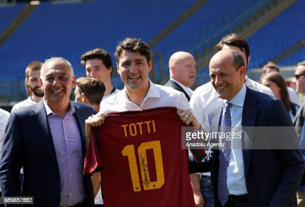 Canada's Prime Minister Justin Trudeau flanked by AS Roma soccer team president James Pallotta and general director Mauro Baldissoni shows a jersey...
