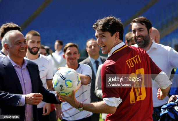 Canada's Prime Minister Justin Trudeau flanked by AS Roma soccer team president James Pallotta wears a jersey signed by Francesco Totti during the...