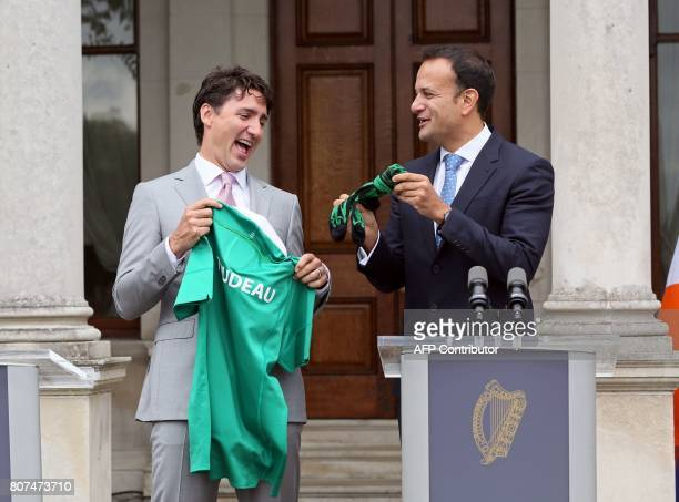 TOPSHOT Canada's Prime Minister Justin Trudeau is presented with an Ireland rugby union shirt and a pair of socks by Ireland's Prime Minister Leo...