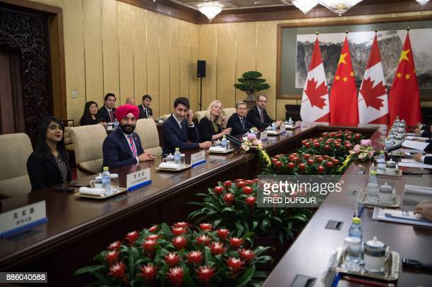 Canada's Prime Minister Justin Trudeau speaks to China's President Xi Jinping during a meeting at the Diaoyutai State Guesthouse in Beijing on...