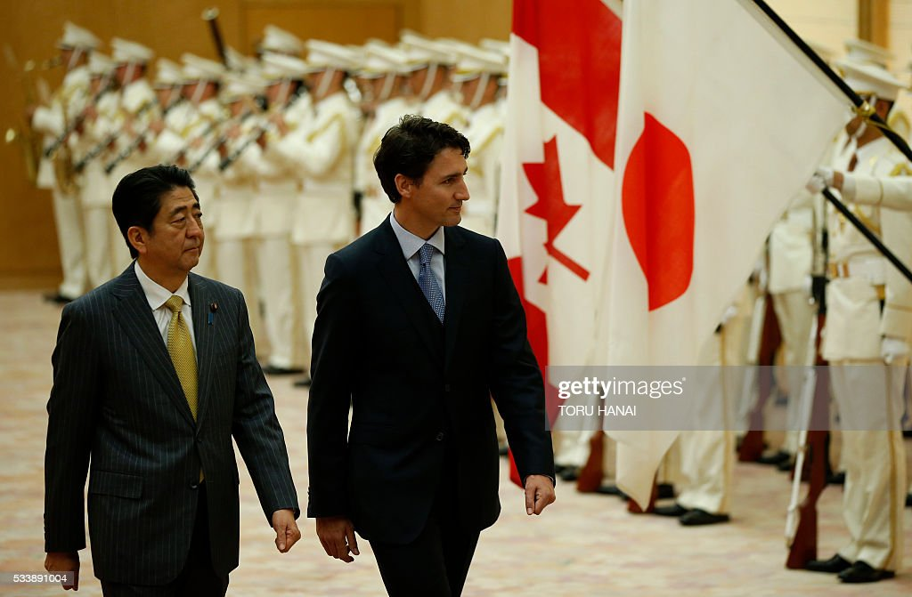 Canada's Prime Minister Justin Trudeau (R) walks with Japan's Prime Minister Shinzo Abe (L) as they review a guard of honour before their meeting at Abe's official residence in Tokyo on May 24, 2016. Trudeau stopped in Tokyo before attending the Ise-Shima G7 Summit on May 26-27. / AFP / POOL / TORU