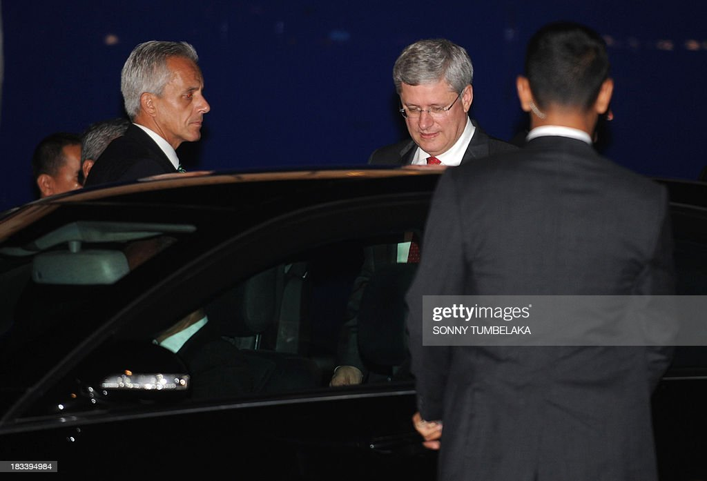 Canada's Prime Minister Stephen Harper (2nd R) gets into a car upon arrival at Ngurah Rai International Airport in Denpasar on the Indonesian resort island of Bali to take part in the Asia-Pacific Economic Cooperation (APEC) summit on October 6, 2013. Leaders of the 21-member APEC grouping are arriving in Bali ahead of the leader's summit on October 7-8 in nearby Nusa Dua.