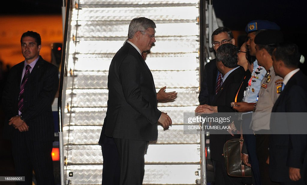 Canada's Prime Minister Stephen Harper (C) is greeted upon arrival at Ngurah Rai International Airport in Denpasar on the Indonesian resort island of Bali to take part in the Asia-Pacific Economic Cooperation (APEC) summit on October 6, 2013. Leaders of the 21-member APEC grouping are arriving in Bali ahead of the leader's summit on October 7-8 in nearby Nusa Dua.