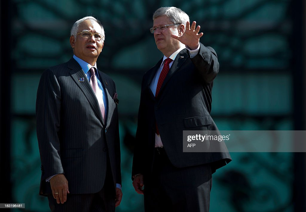 Canada's Prime Minister Stephen Harper (R) speaks with Malaysian Prime Minister Najib Razak (L) during a photo call at the top steps of the prime minister's office in Putrajaya on October 6, 2013. Harper arrived for a visit to hold talks with the Malaysian leadership on bilateral and international issues.