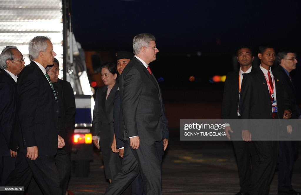 Canada's Prime Minister Stephen Harper (C) walks from his plane upon arrival at Ngurah Rai International Airport in Denpasar on the Indonesian resort island of Bali to take part in the Asia-Pacific Economic Cooperation (APEC) summit on October 6, 2013. Leaders of the 21-member APEC grouping are arriving in Bali ahead of the leader's summit on October 7-8 in nearby Nusa Dua. AFP PHOTO / SONNY TUMBELAKA