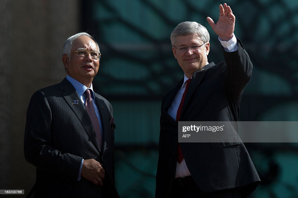 Canada's Prime Minister Stephen Harper (R) waves as Malaysian Prime Minister Najib Razak (L) looks on during a photo call at the top steps of the prime minister's office in Putrajaya on October 6, 2013. Harper arrived for a visit to hold talks with the Malaysian leadership on bilateral and international issues.