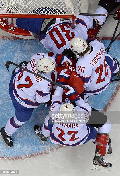 Canada's Rick Nash is pushed by Norways goalkeeper Lars Haugen Martin Roymark Kristian Forsberg and Henrik Oedegaard during the Men's Ice Hockey...