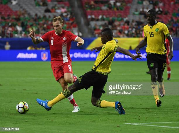 Canada's Scott Arfield is tackled by Jamaica's Cory Burke during their quarterfinal match of the 2017 CONCACAF Gold Cup at the University of Phoenix...