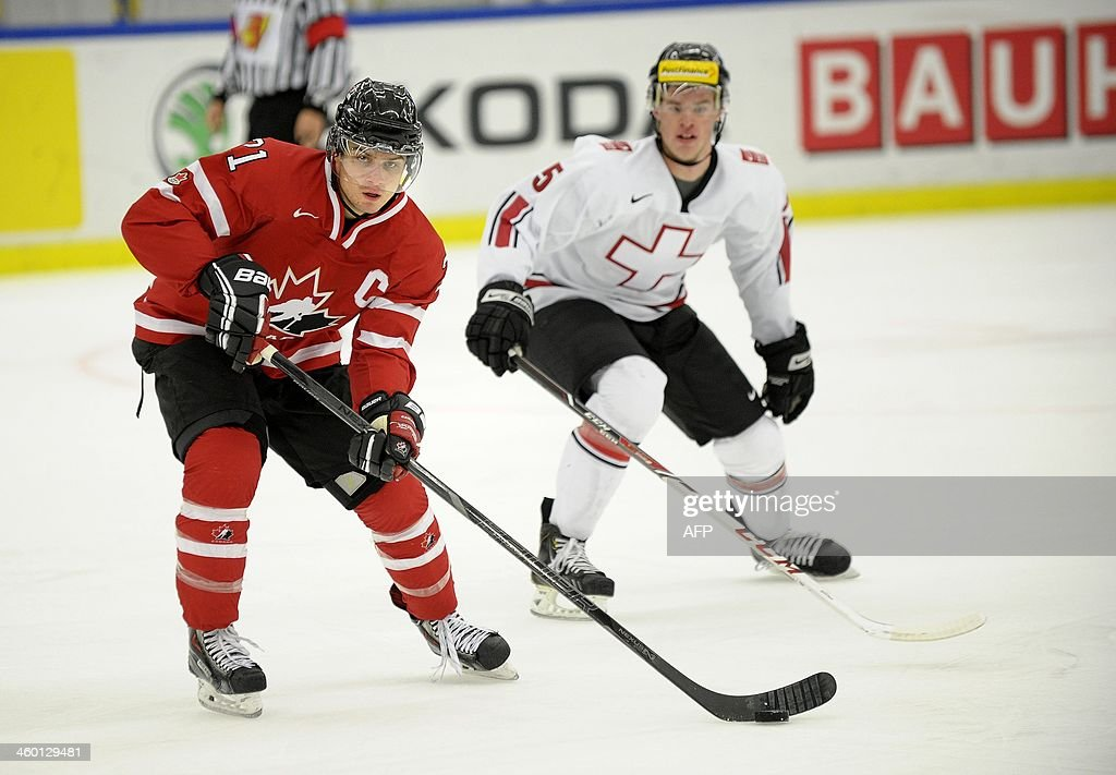 Canada's Scott Laughton (L) controls the puck in front of Switzerland's Mirco Muller in the World Junior Hockey Championships quarter final between Canada and Switzerland at the Malmo Stadium in Malmo, Sweden on January 2, 2014.