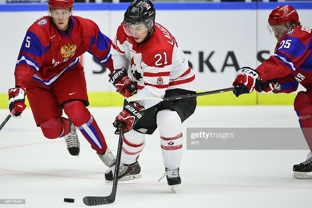 Canada's Scott Laughton (C) vies with Russia's Alexei Bereglazov and Mikhail Grigorenko during the World Junior Hockey Championships bronze medal match between Canada and Russia at Malmo Arena in Malmo, Sweden on January 5, 2014. AFP PHOTO / TT NEWS AGENCY / LUDVIG THUNMAN +++ SWEDEN OUT +++