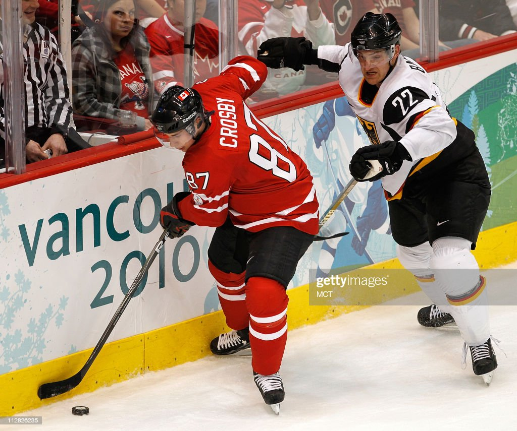Canada's Sidney Crosby keeps the puck away rom Germany's Michael Bakos in the Men's Hockey game during the 2010 Winter Olympics in Vancouver British...