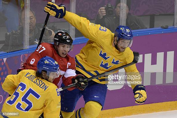Canada's Sidney Crosby vies with Sweden's Erik Karlsson and Sweden's Alexander Edler during the Men's ice hockey final Sweden vs Canada at the...