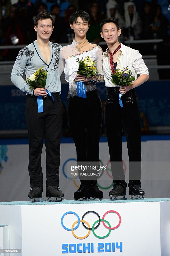 Canada's silver medalist Patrick Chan, Japan's gold medalist Yuzuru Hanyu and Kazakhstan's bronze medalist Denis Ten pose on the podium during the Men's Figure Skating Flower Ceremony at the Iceberg Skating Palace during the Sochi Winter Olympics on February 14, 2014.