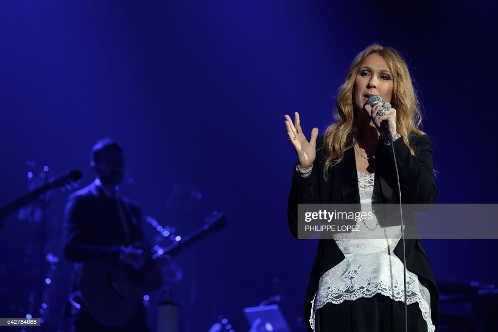 Canada's singer Celine Dion performs on stage, flanked by his guitarist Kaven Girouard (L) at AccorHotels Arena concert hall in Paris on June 24, 2016. / AFP / PHILIPPE